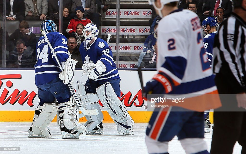 James Reimer #34 and Ben Scrivens #30 of the Toronto Maple Leafs switch after 5th goal by the New York Islanders during NHL action at the Air Canada Centre January 24, 2013 in Toronto, Ontario, Canada.