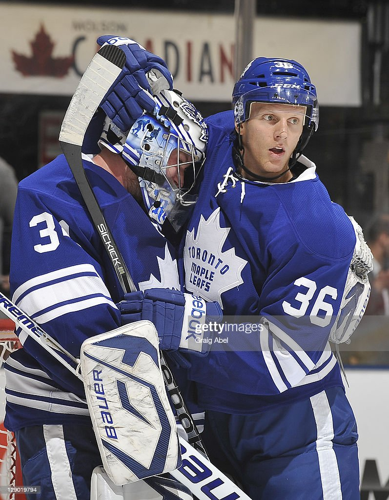 James Reimer and Carl Gunnarsson of the Toronto Maple Leafs celebrate the teams win over the Montreal Canadiens during NHL game action October 6 2011...