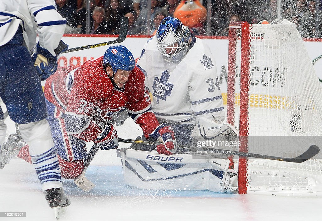 James Reimer #34 and <a gi-track='captionPersonalityLinkClicked' href=/galleries/search?phrase=Dion+Phaneuf&family=editorial&specificpeople=545455 ng-click='$event.stopPropagation()'>Dion Phaneuf</a> #3 of the Toronto Maple Leafs, defend the net against <a gi-track='captionPersonalityLinkClicked' href=/galleries/search?phrase=Travis+Moen&family=editorial&specificpeople=208110 ng-click='$event.stopPropagation()'>Travis Moen</a> #32 of the Montreal Canadiens during the NHL game on October 1, 2013 at the Bell Centre in Montreal, Quebec, Canada.