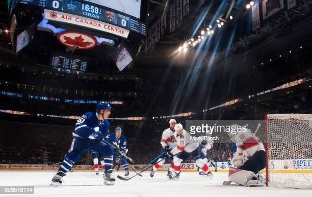 James Reimer of the Florida Panthers makes a save against Jake Gardiner of the Toronto Maple Leafs as Aleksander Barkov of the Florida Panthers ties...