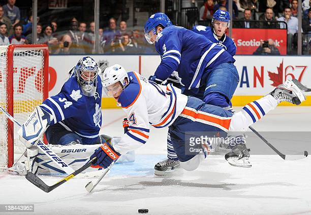 James Reimer of the Toronto Maple Leafs defends the goal as teammate Dion Phaneuf checks Taylor Hall of the Edmonton Oilers during NHL game action...