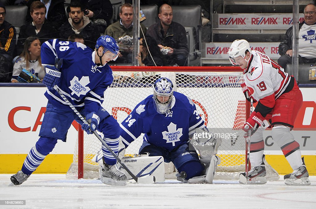 James Reimer #34 of the Toronto Maple Leafs defends the goal as teammate Carl Gunnarsson #36 battles for the puck with Jiri Tlusty #19 of the Carolina Hurricanes during NHL game action March 28, 2013 at the Air Canada Centre in Toronto, Ontario, Canada.
