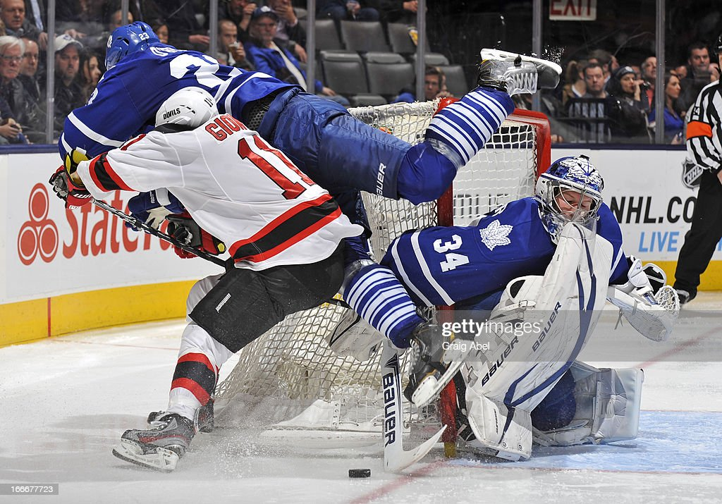 James Reimer #34 of the Toronto Maple Leafs defends the goal as teammate Ryan O'Byrne #23 battles with Stephen Gionta #11 of the New Jersey Devils during NHL game action April 15, 2013 at the Air Canada Centre in Toronto, Ontario, Canada.