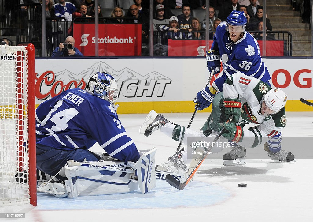 James Reimer #34 of the Toronto Maple Leafs defends the goal as teammate <a gi-track='captionPersonalityLinkClicked' href=/galleries/search?phrase=Carl+Gunnarsson&family=editorial&specificpeople=5557315 ng-click='$event.stopPropagation()'>Carl Gunnarsson</a> #36 battles with <a gi-track='captionPersonalityLinkClicked' href=/galleries/search?phrase=Zach+Parise&family=editorial&specificpeople=213606 ng-click='$event.stopPropagation()'>Zach Parise</a> #11 of the Minnesota Wild during NHL game action October 15, 2013 at Air Canada Centre in Toronto, Ontario, Canada.