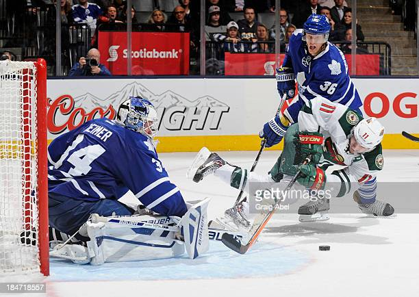 James Reimer of the Toronto Maple Leafs defends the goal as teammate Carl Gunnarsson battles with Zach Parise of the Minnesota Wild during NHL game...
