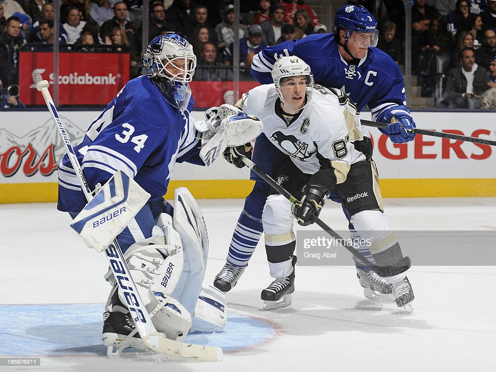 James Reimer #34 of the Toronto Maple Leafs defends the goal as teammate <a gi-track='captionPersonalityLinkClicked' href=/galleries/search?phrase=Dion+Phaneuf&family=editorial&specificpeople=545455 ng-click='$event.stopPropagation()'>Dion Phaneuf</a> #3 battles with <a gi-track='captionPersonalityLinkClicked' href=/galleries/search?phrase=Sidney+Crosby&family=editorial&specificpeople=212781 ng-click='$event.stopPropagation()'>Sidney Crosby</a> #87 of the Pittsburgh Penguins during NHL game action October 26, 2013 at Air Canada Centre in Toronto, Ontario, Canada.
