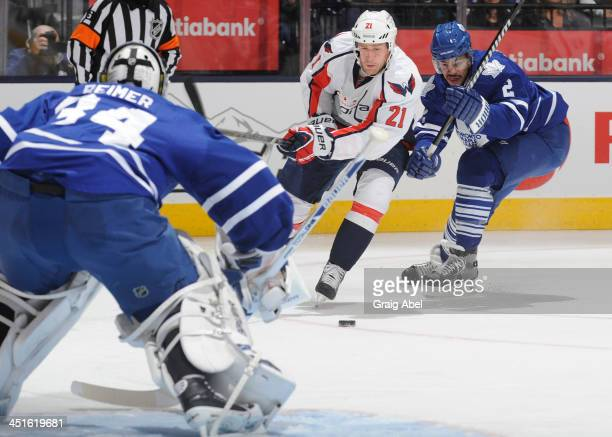 James Reimer of the Toronto Maple Leafs defends the goal as teammate Mark Fraser battles for the puck with Brooks Laich of the Washington Capitals...