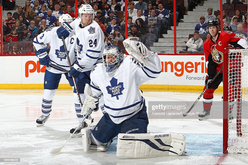 James Reimer #34 of the Toronto Maple Leafs guards his net as Peter Holland #24 and Dion Phaneuf #3 defend against Jason Spezza #19 of the Ottawa Senators on April 12, 2014 at Canadian Tire Centre in Ottawa, Ontario, Canada.