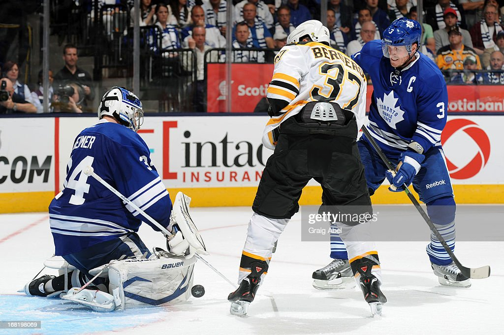 James Reimer #34 of the Toronto Maple Leafs makes a pad save as teammate <a gi-track='captionPersonalityLinkClicked' href=/galleries/search?phrase=Dion+Phaneuf&family=editorial&specificpeople=545455 ng-click='$event.stopPropagation()'>Dion Phaneuf</a> #3 battles with <a gi-track='captionPersonalityLinkClicked' href=/galleries/search?phrase=Patrice+Bergeron&family=editorial&specificpeople=204162 ng-click='$event.stopPropagation()'>Patrice Bergeron</a> #37 of the Boston Bruins in Game Three of the Eastern Conference Quarterfinals during the 2013 NHL Stanley Cup Playoffs May 6, 2013 at the Air Canada Centre in Toronto, Ontario, Canada.