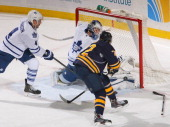 James Reimer of the Toronto Maple Leafs makes a pad save on Luke Adam of the Buffalo Sabres in the third period at First Niagara Center on November...