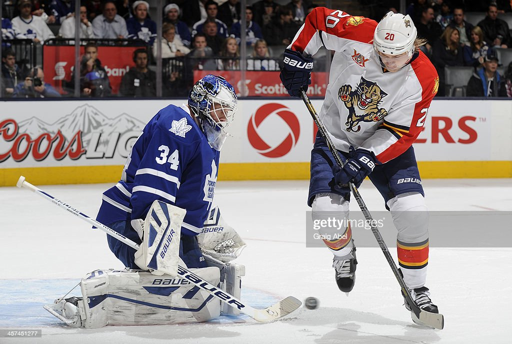James Reimer #34 of the Toronto Maple Leafs makes a pad save with <a gi-track='captionPersonalityLinkClicked' href=/galleries/search?phrase=Sean+Bergenheim&family=editorial&specificpeople=208830 ng-click='$event.stopPropagation()'>Sean Bergenheim</a> #20 of the Florida Panthers on the doorstep during NHL game action December 17, 2013 at the Air Canada Centre in Toronto, Ontario, Canada.