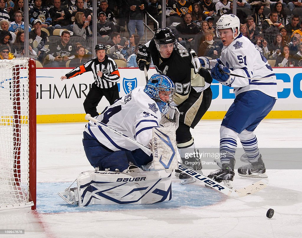 James Reimer #34 of the Toronto Maple Leafs makes a save in front of Sidney Crosby #87 of the Pittsburgh Penguins and Jake Gardiner #51 of the Maple Leafs on January 23, 2013 at Consol Energy Center in Pittsburgh, Pennsylvania.