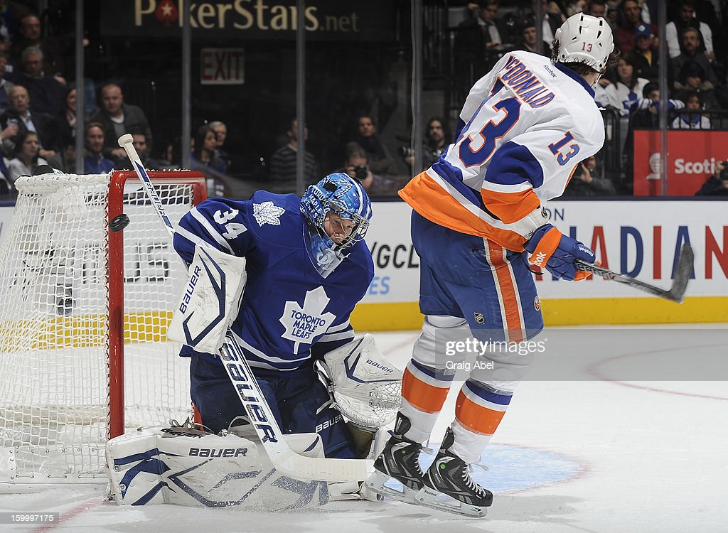 James Reimer #34 of the Toronto Maple Leafs makes a shoulder save with Colin McDonald #13 of the New York Islanders on the doorstep during NHL game action January 24, 2013 at the Air Canada Centre in Toronto, Ontario, Canada.