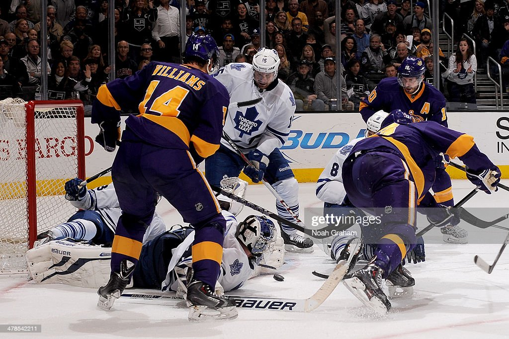 James Reimer #34 of the Toronto Maple Leafs reaches for the puck against Justin Williams #14 of the Los Angeles Kings at Staples Center on March 13, 2014 in Los Angeles, California.