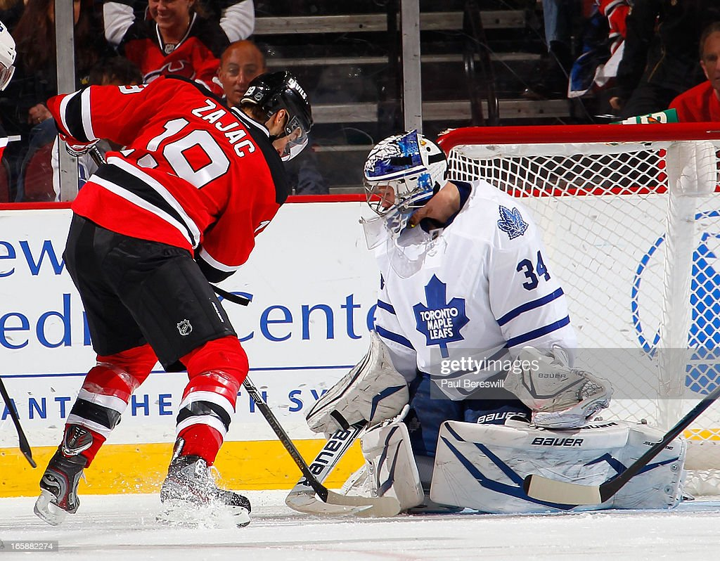 James Reimer #34 of the Toronto Maple Leafs stops <a gi-track='captionPersonalityLinkClicked' href=/galleries/search?phrase=Travis+Zajac&family=editorial&specificpeople=864182 ng-click='$event.stopPropagation()'>Travis Zajac</a> #19 of the New Jersey Devils during the first period of an NHL hockey game at Prudential Center on April 6, 2013 in Newark, New Jersey. The Leafs won 2-1.