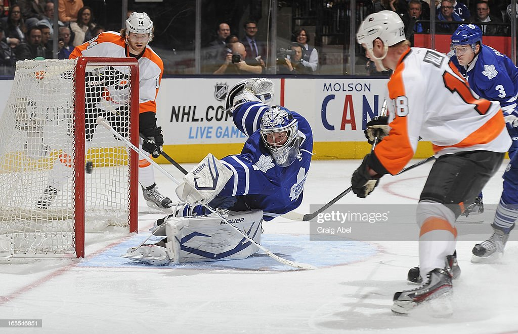 James Reimer #34 of the Toronto Maple Leafs stretches to make a save as <a gi-track='captionPersonalityLinkClicked' href=/galleries/search?phrase=Sean+Couturier&family=editorial&specificpeople=5663953 ng-click='$event.stopPropagation()'>Sean Couturier</a> #14 and <a gi-track='captionPersonalityLinkClicked' href=/galleries/search?phrase=Adam+Hall+-+Ice+Hockey+Player&family=editorial&specificpeople=202919 ng-click='$event.stopPropagation()'>Adam Hall</a> #18 of the Philadelphia Flyers look on during NHL game action April 4, 2013 at the Air Canada Centre in Toronto, Ontario, Canada.