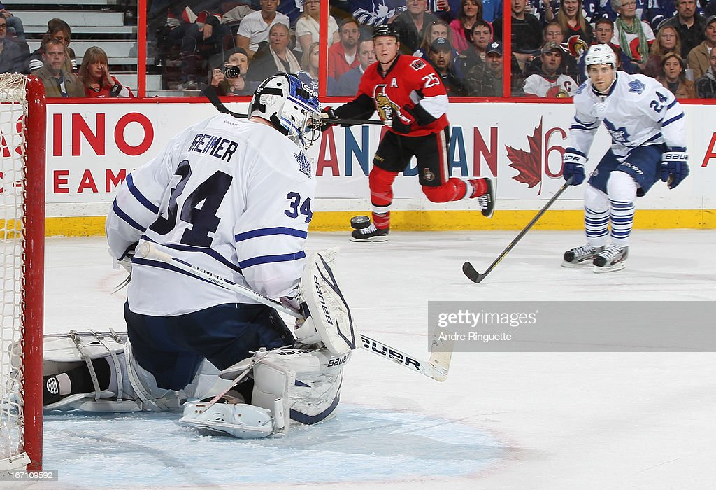 James Reimer #34 of the Toronto Maple Leafs watches the rebound after making a save on a shot by Chris Neil #25 of the Ottawa Senators as John-Michael Liles #24 follows on the play on April 20, 2013 at Scotiabank Place in Ottawa, Ontario, Canada.