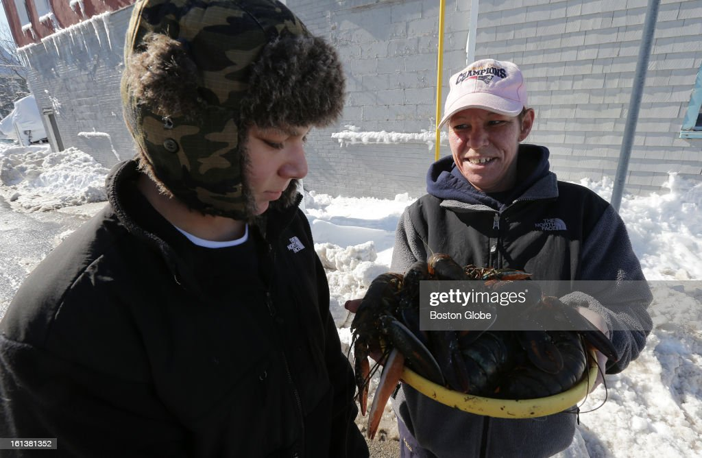 James Richardson, 16, left, and Stacie Molvar, both of Hull, with a slew of live and kicking lobsters they found washed ashore while walking on Nantasket beach in Hull on Sunday, Feb. 10, 2013, after a blizzard hit New England.