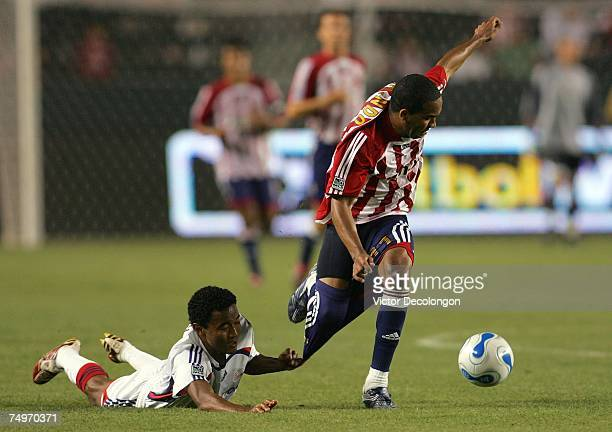 James Riley of the New England Revolution hangs on to the shorts of Maykel Galindo of Chivas USA as Galindo dribbles the ball to midfield during...