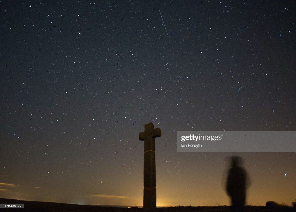 James Ritson looks skywards as a meteor streaks across the night sky above New Ralph's Cross on August 13, 2013 over the North Yorkshire Moors, United Kingdom. The Perseid Meteor shower is visible from mid-july each year with peak activity being between the 9th and 14th of August. During the peak, the rate of meteors can reach 60 or more per hour. They can be seen all across the sky as they gradually fall away from the tail of the Swift-Tuttle comet.