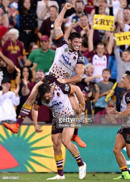 James Roberts of the Broncos celebrates with team mate Matt Gillett after scoring the match winning try during the round seven NRL match between the...