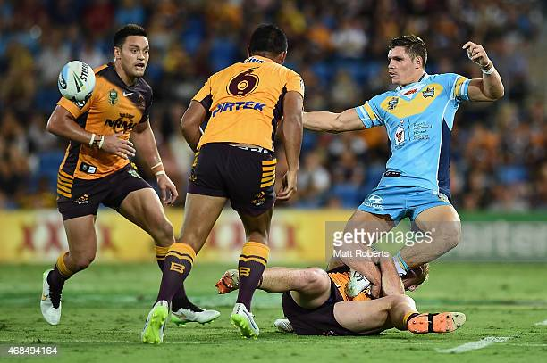 James Roberts of the Titans offloads the ball in the tackle during the round five NRL match between the Gold Coast Titans and the Brisbane Broncos at...