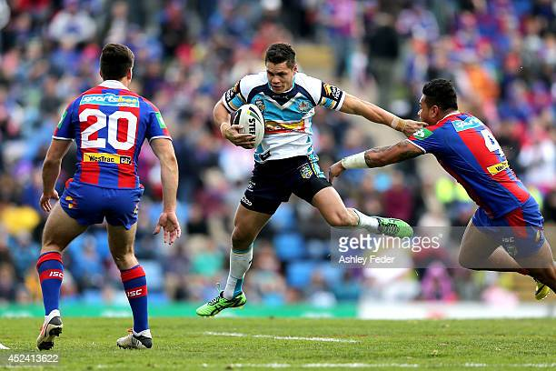 James Roberts of the Titans runs past the Knights defence during the round 19 NRL match between the Newcastle Knights and Gold Coast Titans at Hunter...