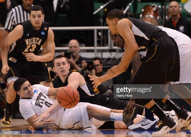 James Robinson of the Pittsburgh Panthers and Jake White of the Wichita State Shockers battle for a loose ball during the second round of the 2013...