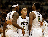 James Robinson of the Pittsburgh Panthers hugs teammates Jamel Artis and Michael Young in the second half against the Notre Dame Fighting Irish...