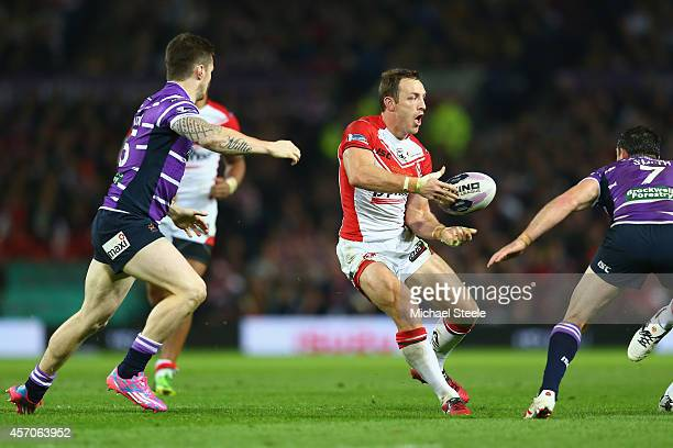 James Roby of St Helens feeds a pass as Anthony Gelling and Matty Smith of Wigan close in during the First Utility Super League Grand Final match...