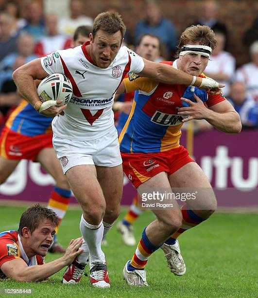 James Roby of StHelens is tackled by Jason Golden and Andy Ellis during the Engage Super League match between St Helens and Harlequins RL at Knowsley...