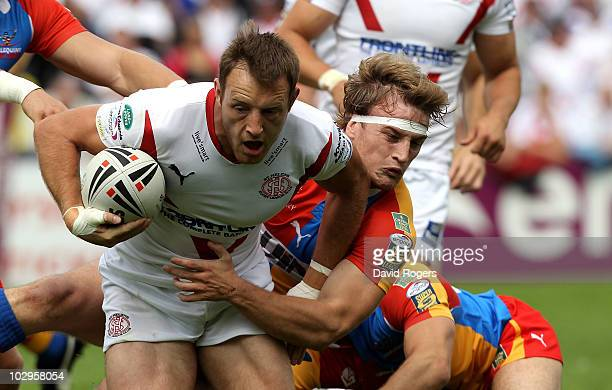 James Roby of StHelens is tackled by Jason Golden during the Engage Super League match between St Helens and Harlequins RL at Knowsley Road on July...