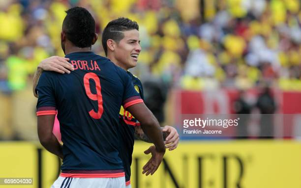 James Rodríguez of Colombia celebrates with teammate Miguel Borja after scoring the opening goal during a match between Ecuador and Colombia as part...
