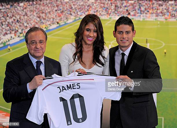 James Rodriguez holds his new Real shirt beside club president Florentino Perez and his wife Daniela Ospina during his unveiling as a new Real Madrid...