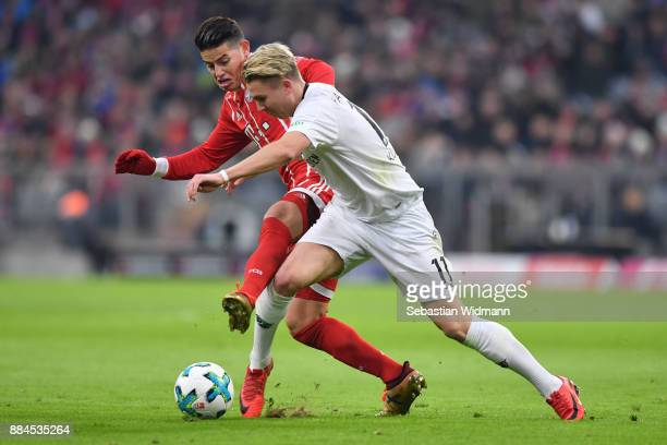 James Rodriguez of Bayern Muenchen and Felix Klaus of Hannover compete for the ball during the Bundesliga match between FC Bayern Muenchen and...