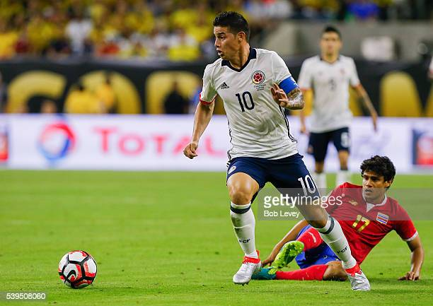 James Rodriguez of Colombia brings the ball up the field as Yeltsin Tejeda of Costa Rica falls down at NRG Stadium on June 11 2016 in Houston Texas