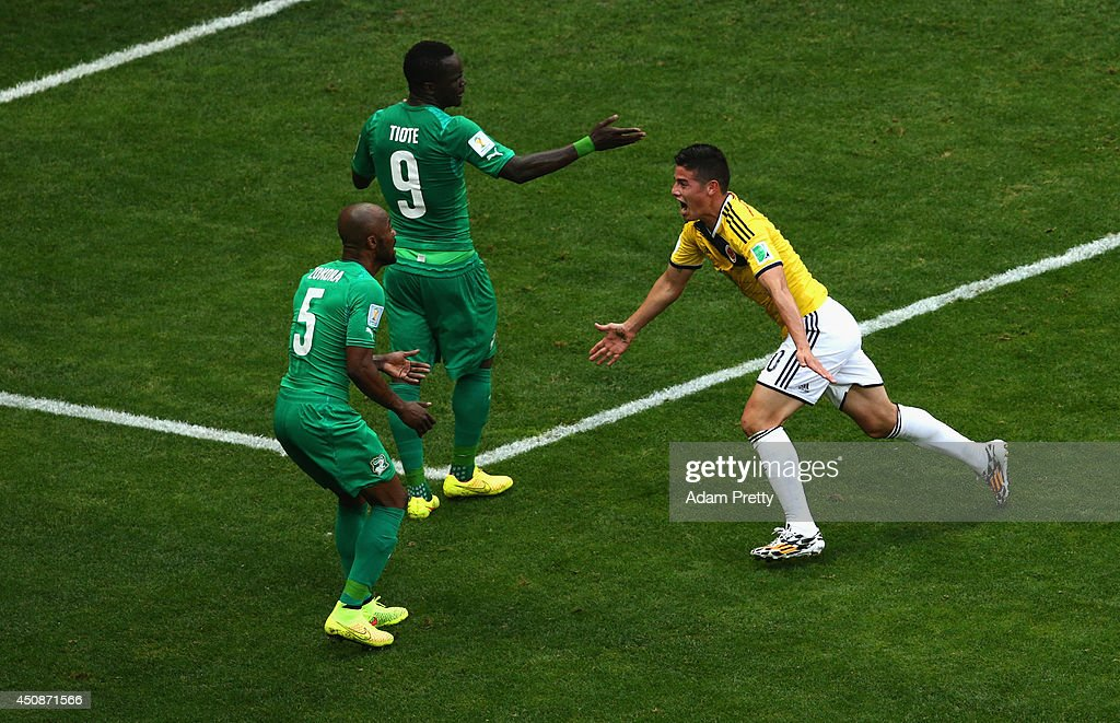 <a gi-track='captionPersonalityLinkClicked' href=/galleries/search?phrase=James+Rodriguez&family=editorial&specificpeople=4422074 ng-click='$event.stopPropagation()'>James Rodriguez</a> of Colombia celebrates scoring his team's first goal as <a gi-track='captionPersonalityLinkClicked' href=/galleries/search?phrase=Didier+Zokora&family=editorial&specificpeople=550698 ng-click='$event.stopPropagation()'>Didier Zokora</a> and <a gi-track='captionPersonalityLinkClicked' href=/galleries/search?phrase=Cheick+Tiote&family=editorial&specificpeople=5490367 ng-click='$event.stopPropagation()'>Cheick Tiote</a> of the Ivory Coast look on during the 2014 FIFA World Cup Brazil Group C match between Colombia and Cote D'Ivoire at Estadio Nacional on June 19, 2014 in Brasilia, Brazil.