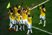 James Rodriguez of Colombia celebrates scoring his team's second goal and his second of the game with teammates during the 2014 FIFA World Cup Brazil...