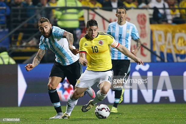 James Rodriguez of Colombia fights for the ball with Nicolas Otamendi of Argentina during the 2015 Copa America Chile quarter final match between...