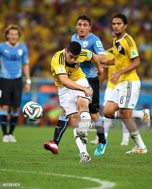 James Rodriguez of Colombia shoots and scoores his team's first goal during the 2014 FIFA World Cup Brazil round of 16 match between Colombia and...