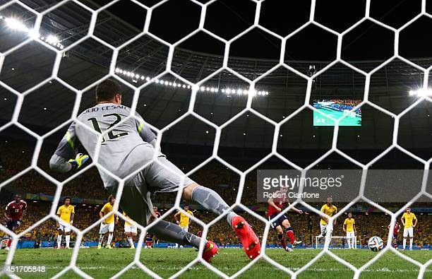 James Rodriguez of Colombia shoots and scores his team's first goal on a penalty kick past Julio Cesar of Brazil during the 2014 FIFA World Cup...