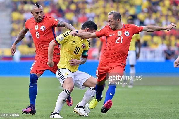 James Rodriguez of Colombia struggles for the ball with Arturo Vidal and Marcelo Diaz of Chile during a match between Colombia and Chile as part of...