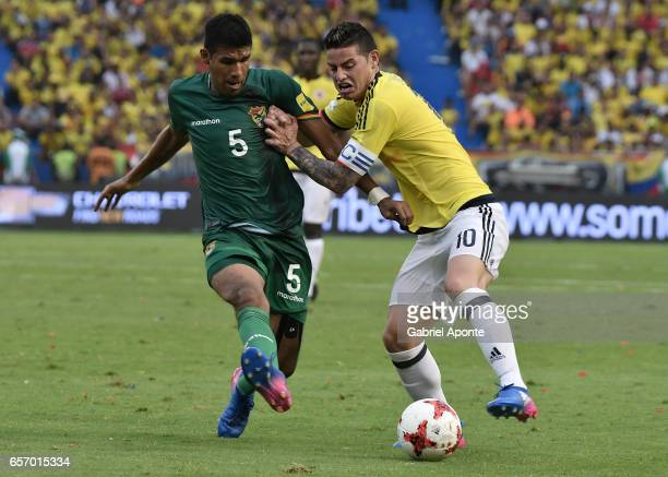 James Rodriguez of Colombia struggles for the ball with Mario Cuellar of Bolivia during a match between Colombia and Bolivia as part of FIFA 2018...
