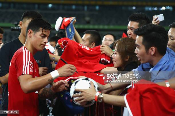 James Rodriguez of FC Bayern Muenchen signs autographs after a training session at Shenzhen Universiade Sports Centre during the Audi Summer Tour...