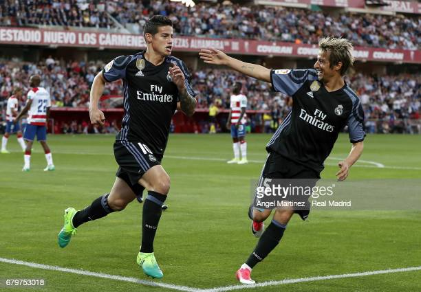 James Rodriguez of Real Madrid celebrates with Fabio Coentrao after scoring their team's second goal during the La Liga match between Granada CF and...