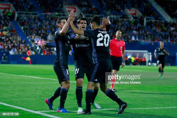 James Rodriguez of Real Madrid CF celebrates scoring their opening goal with teammates Alvaro Morata and Marco Asensio during the La Liga match...