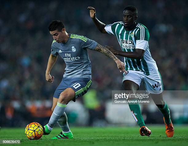 James Rodriguez of Real Madrid CF competes for the ball with Alfred N Diaye of Real Betis Balompie during the La Liga match between Real Betis...