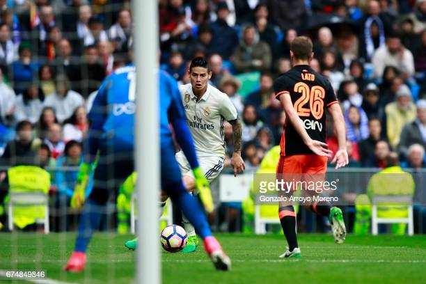James Rodriguez of Real Madrid CF competes for the ball with Antonio Latorre alias Lato and his teammate goalkeeper Diego Alves during the La Liga...