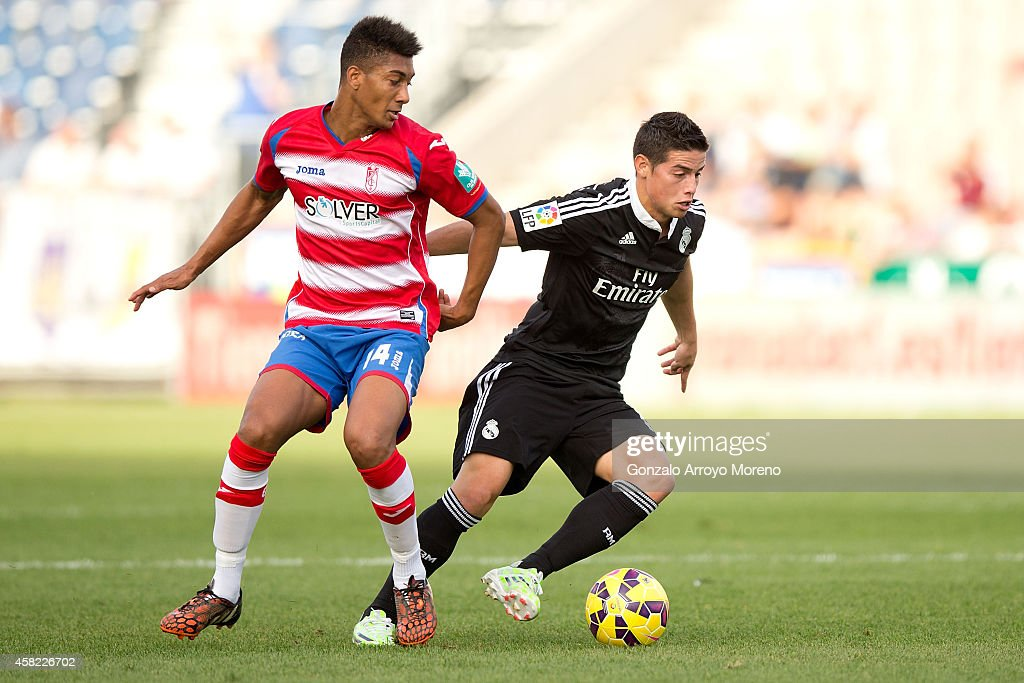 James Rodriguez of Real Madrid CF competes for the ball with Eddy Silvestre of Granada CF during the La Liga match between Granada CF and Real Madrid...