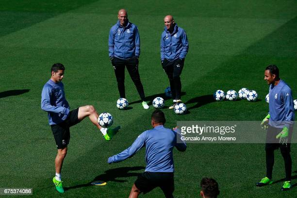James Rodriguez of Real Madrid CF excersises with his teammates Carlos Casemiro and goalkeeper Keylor Navas ahead their coach Zinedine Zidane druing...